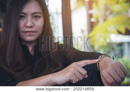 An Asian business woman pointing at a black wristwatch on her arm in working time while waiting for someone with feeling angry