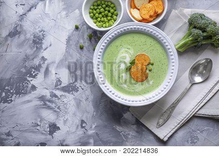 Composition with broccoli soup with rucks on grey background