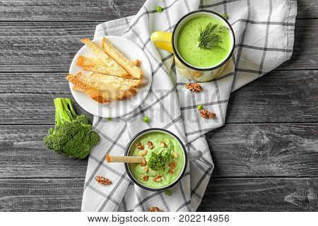 Composition with delicious broccoli soup in mugs on wooden table