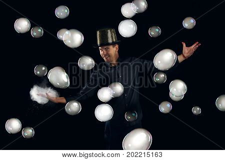 Man artist fiddle with many gel soap bubble. Soap bubble show in black studio.