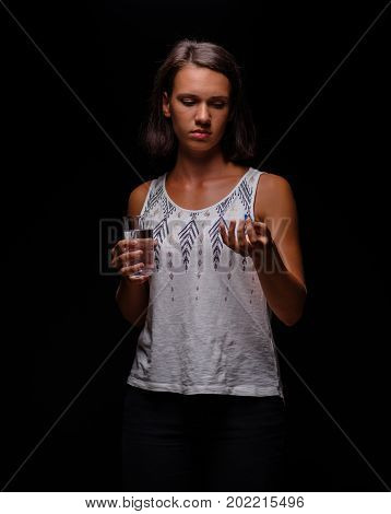 A stressed student girl taking prescripted antidepressants on the black background. Attractive, casual young female with antibiotics or aspirin and fresh water. A sad brunette lady taking medicine.