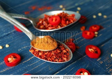 Composition with red chili powder, flakes in metal spoons on blue wooden table