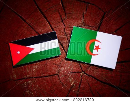 Jordanian Flag With Algerian Flag On A Tree Stump Isolated