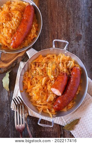 Braised sauerkraut and smoked sausages in two vintage metal bowl on wooden background. Top view rustic style