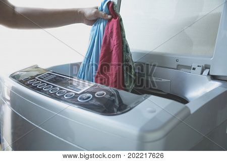Preparing the wash cycle. Washing machine Hand with clothes into the washing machine.