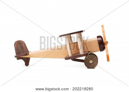 A close-up picture of a brown wooden toy airplane, isolated on a white background. A miniature toy airplane for children games. A developing plaything a symbol of travel and dreams. Copy space.