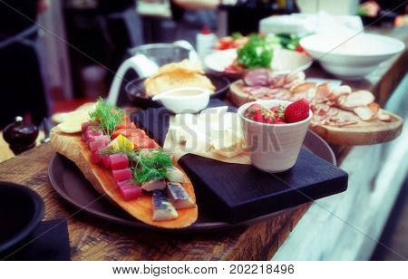 Platter of food on restaurant counter waiting to ba carried to guests, toned image