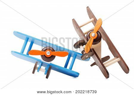 A close-up picture of two wooden toy airplanes, isolated on a white background. Small colorful air vehicle with a propeller for children games. Education and development concept. Copy space.