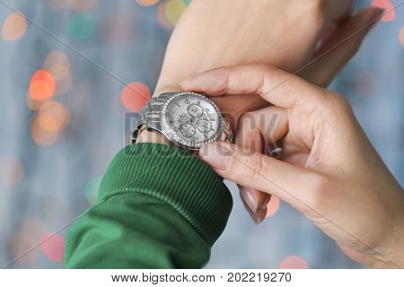 Hands of woman with watch against defocused lights. Christmas countdown concept
