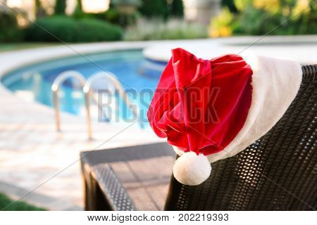 Santa hat on sun lounger near swimming pool at resort. Christmas concept