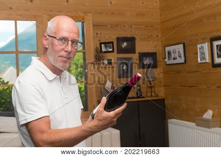 a mature man with bottle of red wine at home