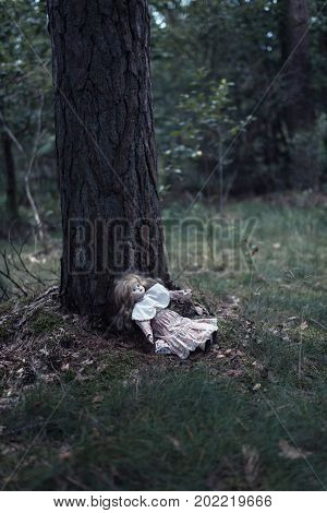 Spooky Doll Girl On Forest Ground Against Tree Trunk.
