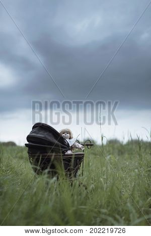 Spooky Doll In Pram Standing In Field Under Dark Stormy Sky.