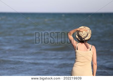 Woman With Straw Hat In Front Of The Sea