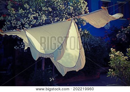 bed sheets spread to dry in the sun in a small village in the mediterranean area