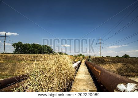 A Large Water Supply Pipe Lies On A Bridge Through A Water Channel