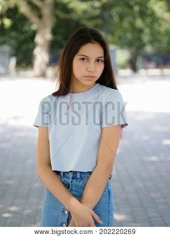 Close-up portrait of a confident, wonderful young lady wearing a blue T-shirt and denim skirt on a street blurred background. A trendy adolescence girl posing in the outdoors. Stylish, youth concept.