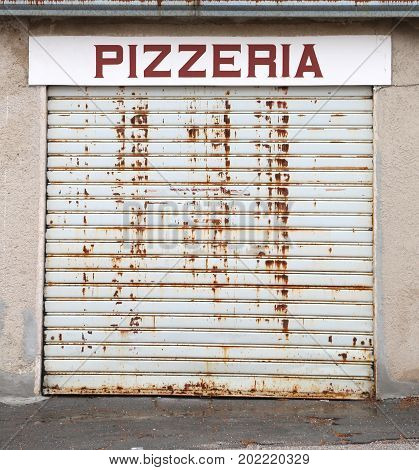 Sign With Pizzeria Text With The Gate Closed Because Of The Econ