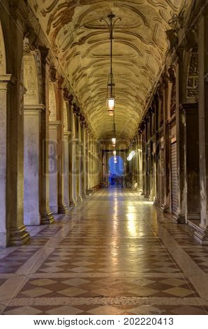 A passageway in Venice with natural evening and artificial light.