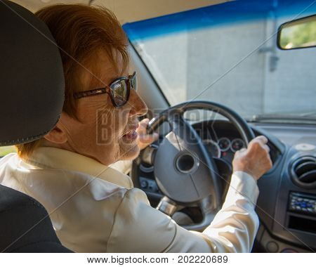 woman in the age of driving a car. Age eighty years.