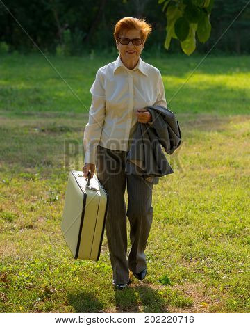 woman aged with a suitcase in her hand is walking along the road. Age eighty years.