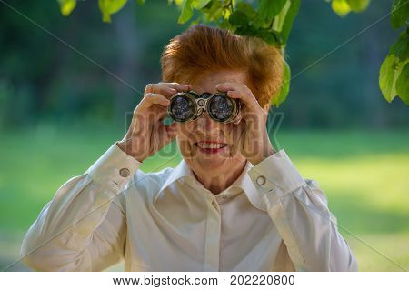 Aged woman looking through binoculars in a park. Age eighty years.