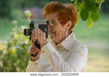woman ages shoots a movie camera park. Age eighty years.