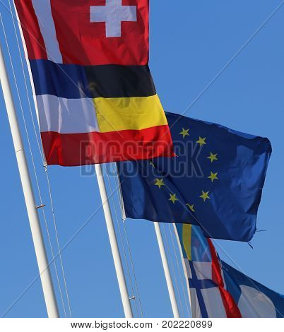 International Flags Waving On The Wind And Blue Sky On Backgroun