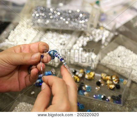 Hand Of Woman As She Wraps Beads In Craft Bracelet