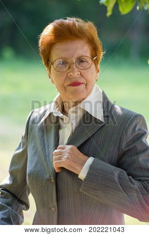 Portrait of a business woman aged correcting a suit. Age eighty years. A woman in a business suit.