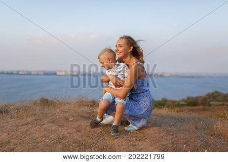 A photo of a gorgeous mother and her handsome little son relaxing on a blurred natural background. A happy family sitting near a blue river and looking on a fantastic nature. Mother and son concept.