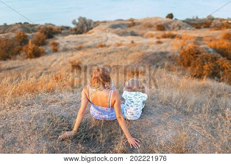 A photo of a lovely female and her handsome little son relaxing on a natural background. A happy family sitting on a field and looking on a fantastic nature. Mother, son, parenthood concept.
