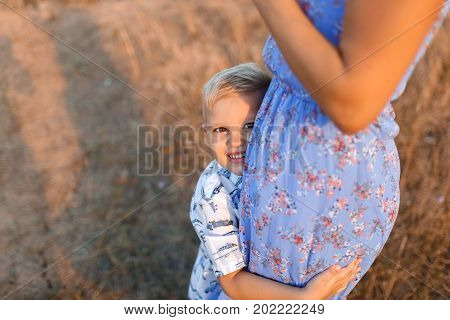 A close-up photo of a joyful blond boy hugging his lovely mother on a blurred natural background. A pretty little child with mom playing on a field. A family walking together in the outdoors.