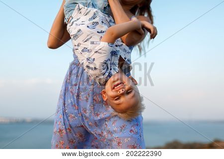 A close-up photo of a young mother and her little child playing with each other on a blurred sky background. Delighted, smiling young mom with a little baby boy on nature. Copy space.