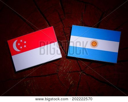 Singaporean Flag With Argentinian Flag On A Tree Stump Isolated