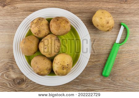 Raw Unpeeled Potatoes In Plate And Vegetable Peeler On Table