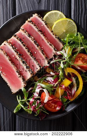 Seared Ahi Tuna Coated Sesame Seeds With Salad On Black Plate Closeup. Top View Vertical