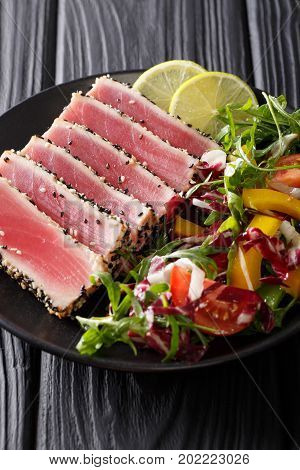 Seared Ahi Tuna Coated Sesame Seeds With Salad On Black Plate Closeup. Vertical