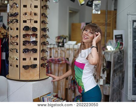 A shopaholic on a blurred shop background. A portrait of a smiling happy girl standing in a shopping center and trying on colorful stylish glasses. Summer accessories. Shopping, fashion concept.