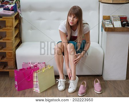 A woman sitting on a sofa and choosing a perfect pair of shoes on a shop background. A female holding trendy pink moccasins in a luxury boutique. Fashionable girl with bright shopping bags in a store.
