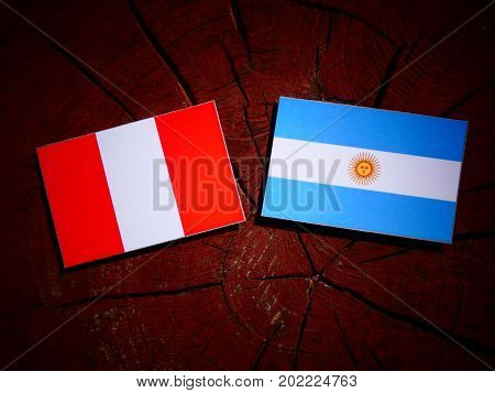 Peruvian Flag With Argentinian Flag On A Tree Stump Isolated
