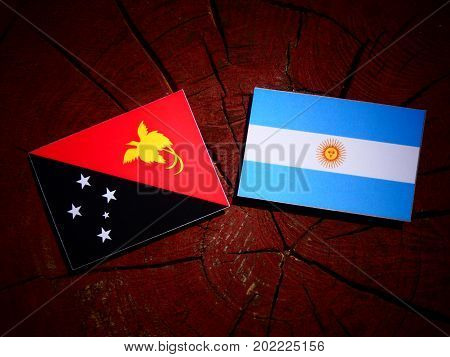Papua New Guinea Flag With Argentinian Flag On A Tree Stump Isolated