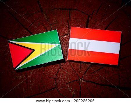 Guyana Flag With Austrian Flag On A Tree Stump Isolated
