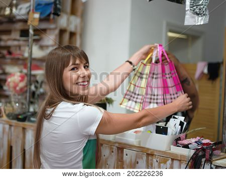 A portrait of a satisfied woman standing in a clothing store with shopping bags on a blurred background. A charming female purchases of stylish clothes in a shop. Consumerism, money, shopping concept.