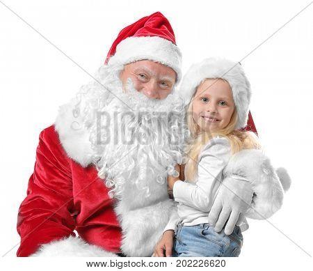 Cute little girl in Christmas hat sitting on Santa's lap against white background