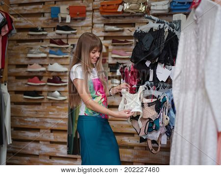 A close-up portrait of a charming woman on a blurred store background. A young female choosing herself a fantastic sexy colorful underwear in a clothing shop and check a quality. Shopping concept.