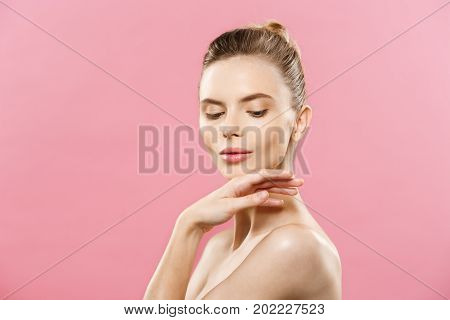 Beauty skin Concept - Beautiful Young Caucasian Woman with Clean Fresh Skin look away with pink studio background. Girl beauty face care. Facial treatment. Cosmetology beauty and spa.