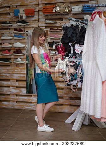 A full-length photo of a charming woman on a blurred store background. A young female choosing herself a fantastic sexy colorful underwear in a clothing shop and check a quality. Shopping concept.