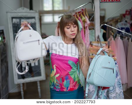 Close-up photo of a thoughtful female choosing herself a light backpack in a clothing store. A young woman holding two beautiful brief bags on a blurred shop background. Accessories, fashion concept.