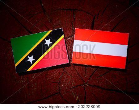 Saint Kitts And Nevis Flag With Austrian Flag On A Tree Stump Isolated